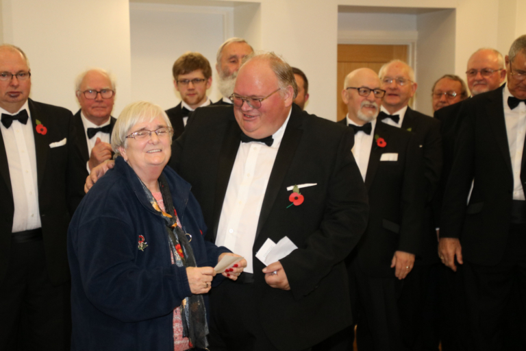 Choir Chairman Nigel Morgan presenting a donation to the Secretary of the Ynyshir Branch of the Royal British Legion, Angela Cutter.